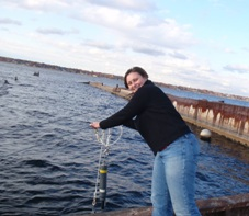 Angie Defore lowering a water quality sonde into Muskegon Lake